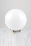 White glass ball table lamp on 3 small ball feet. Contract&More.